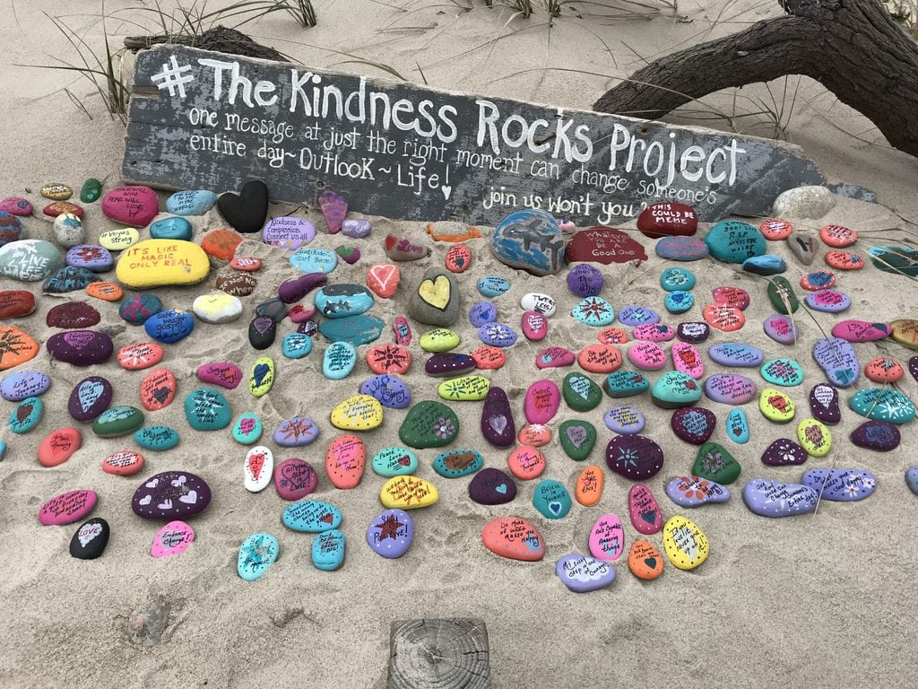 The Kindness Rock Project - painted rocks arranged in the sand