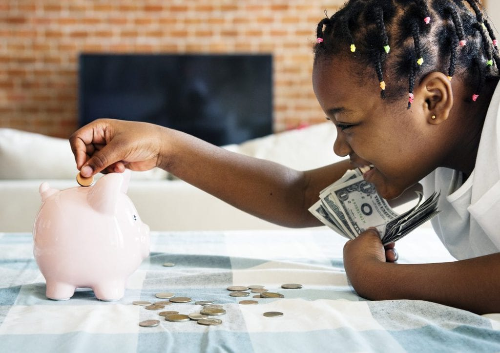 Girl putting money in a piggy bank