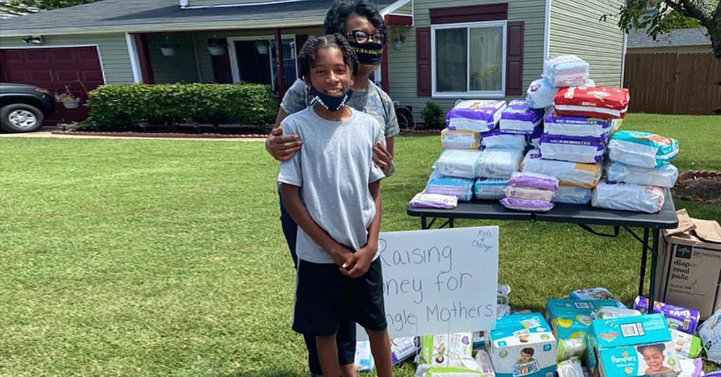Cartier and his mom next to their lemonade/diaper stand