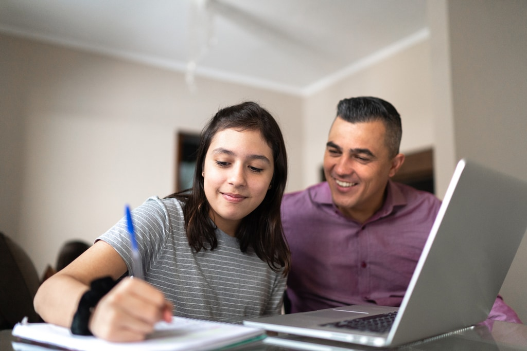 Father helping daughter studying using laptop at home