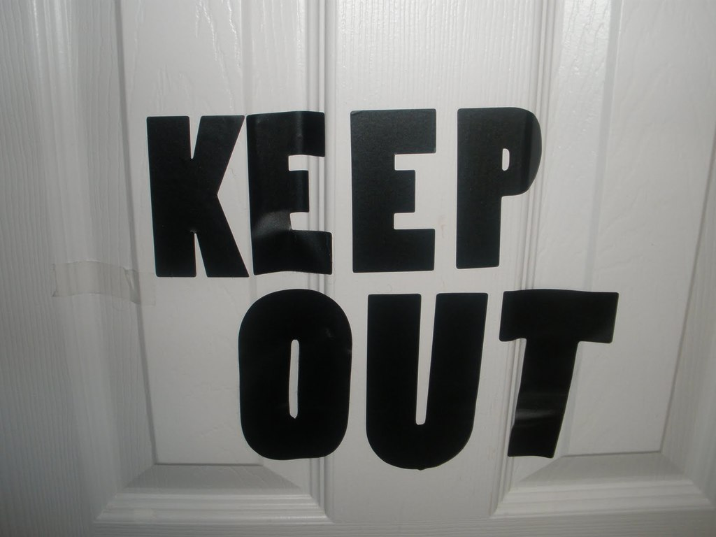 "a sign saying ""Keep Out"" on a door"