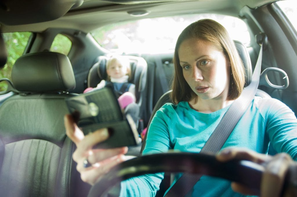 Woman using her phone while driving with her toddler in the back seat