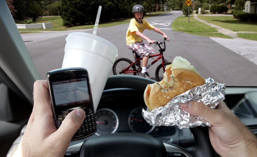Person holding their phone and food while behind the wheel with a young boy crossing the street in front